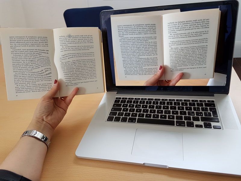 Figure 1: A possible implementation of the technology:  A computer helps a user with distorted vision to read a book by improving their visual perception.