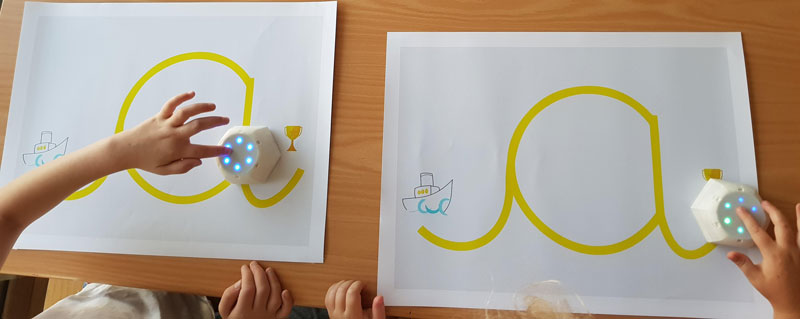 Figure 1: Robot-assisted writing activity with Cellulo: Children interact with the haptic-enabled Cellulo robots on maps displaying the grapheme of a cursive letter, where the start and end of the letter are indicated with a starting cue and a trophy respectively. After three different sub-activities where the robots provide a range of sensory information, a final team activity in the form of a guessing game is played.