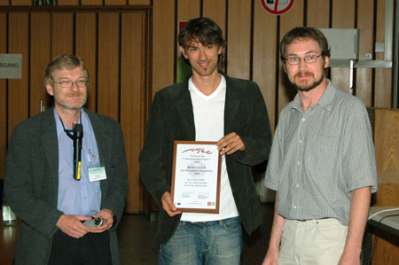 Marco Reisert (centre) receives the prize from competition organisers Michael Nölle (left) and Allan Hanbury (right).