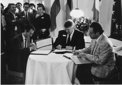 The birth of ERCIM: From left - Alain Bensoussan, INRIA, Friedrich Winkelhage, GMD (on behalf of Gerhard Seegmüller)  and Cor Baayen, CWI, sign the joint agreement on 13 April 1989.